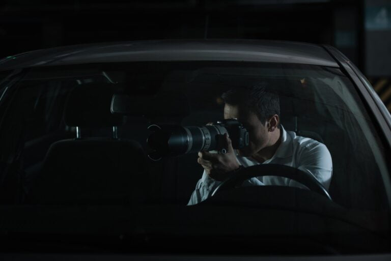male private detective spying by camera with object glass from his car
